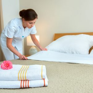 Maid Making Bed In Hotel Room